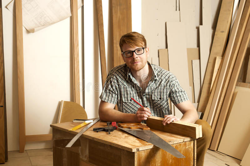 Joiner. The young joiner works on the drawing of a new product royalty free stock photography