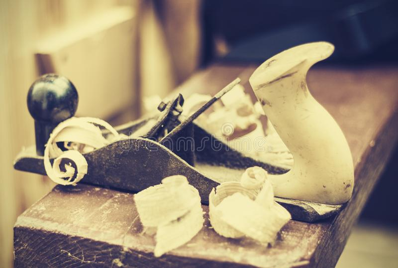 Joinery – old wooden plane and chips in a workshop of the carpenter, retro concept royalty free stock images