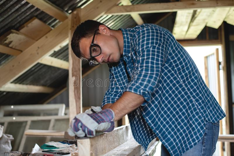 Joinery. The carpenter planes the wood in the workshop. Woodworking, roofing, diy. royalty free stock photos