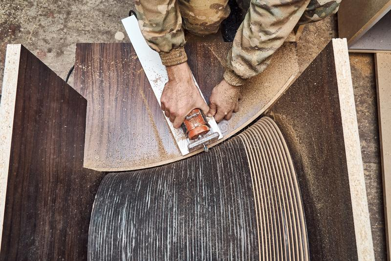Joinery. Faceless carpenter producing wooden coffee table in workshop. Joinery. Unrecognizable craftsman using professional tool for woodwork while making round stock photo