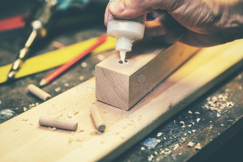 Joinery - joiner put the glue into a drilled hole for wooden dowel joint stock photography