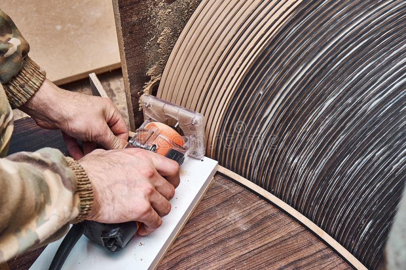 Joinery. Faceless carpenter producing wooden coffee table in workshop. Joinery. Unrecognizable craftsman using professional tool for woodwork while making round stock photos