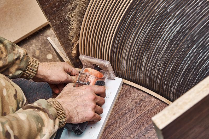 Joinery. Faceless carpenter producing wooden coffee table in workshop. Joinery. Unrecognizable craftsman using professional tool for woodwork while making round stock image