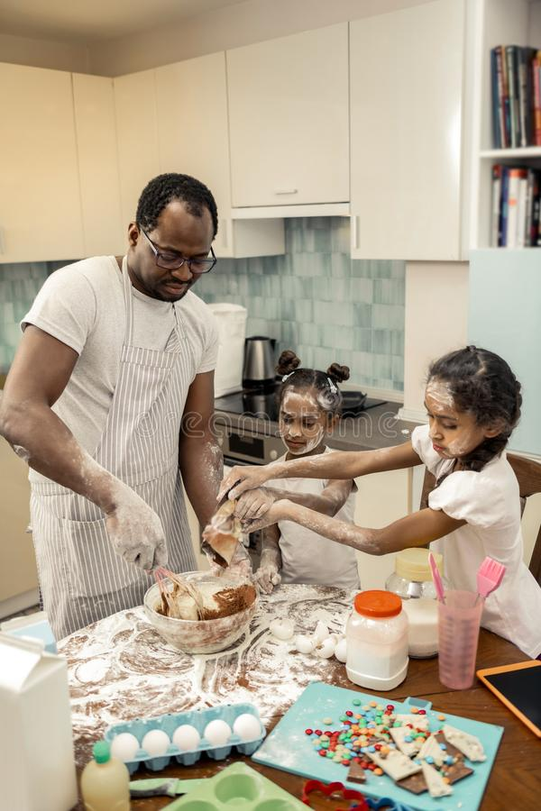 Top view of cute little daughters joining their father cooking pie. Joining father. Top view of cute little beautiful daughters joining their father cooking pie stock photo