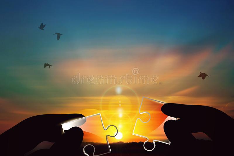 Joining two pieces of glass puzzle against sunset background stock photos