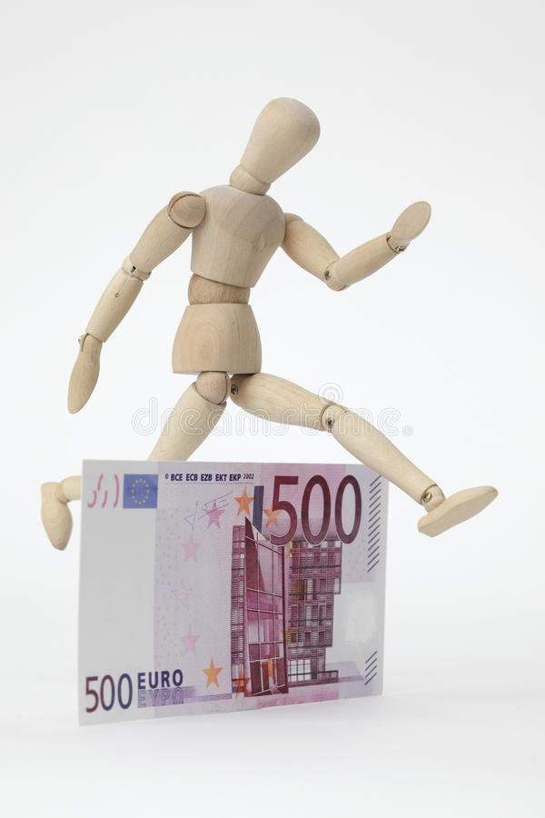 Jointed doll jumping over a 500-Euro-Banknote royalty free stock photos