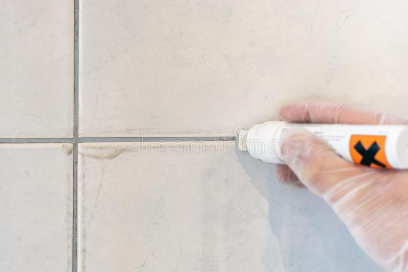 Cleaning a tile joint with a joint pin royalty free stock photos