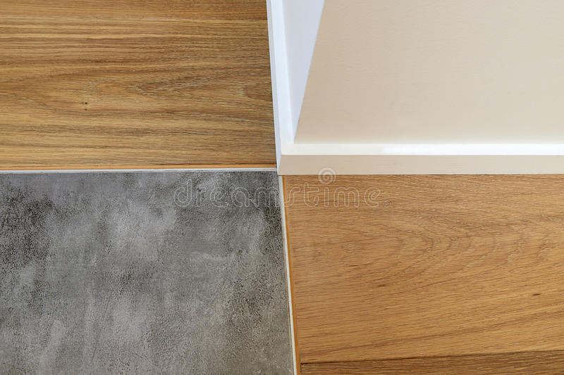 Joints between wood, baseboards and stone floor. Close up on joints between wood, baseboards and stone floor royalty free stock photo