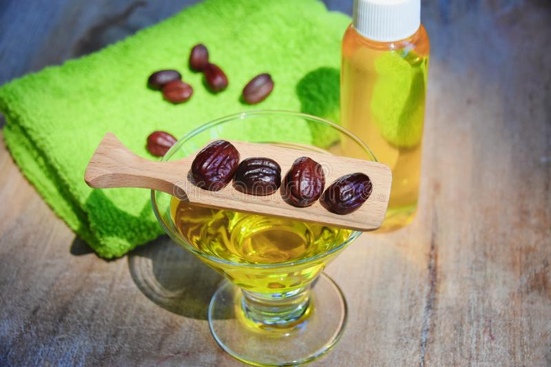Jojoba oil and seeds on a wood surface stock photography