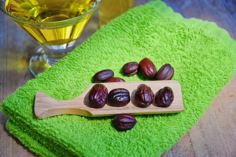 Jojoba oil and seeds on a wood surface stock photos