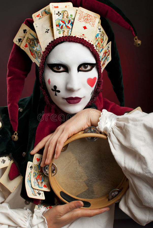 Joker. Girl with a mask painted in the costume joker royalty free stock photography