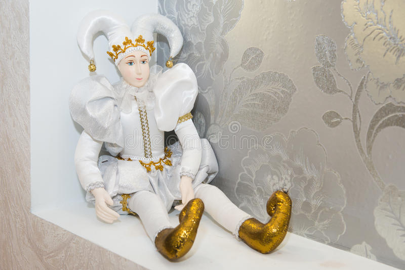 Joker doll, isolated on white background. Doll harlequin, decoration of the hall, royalty free stock images