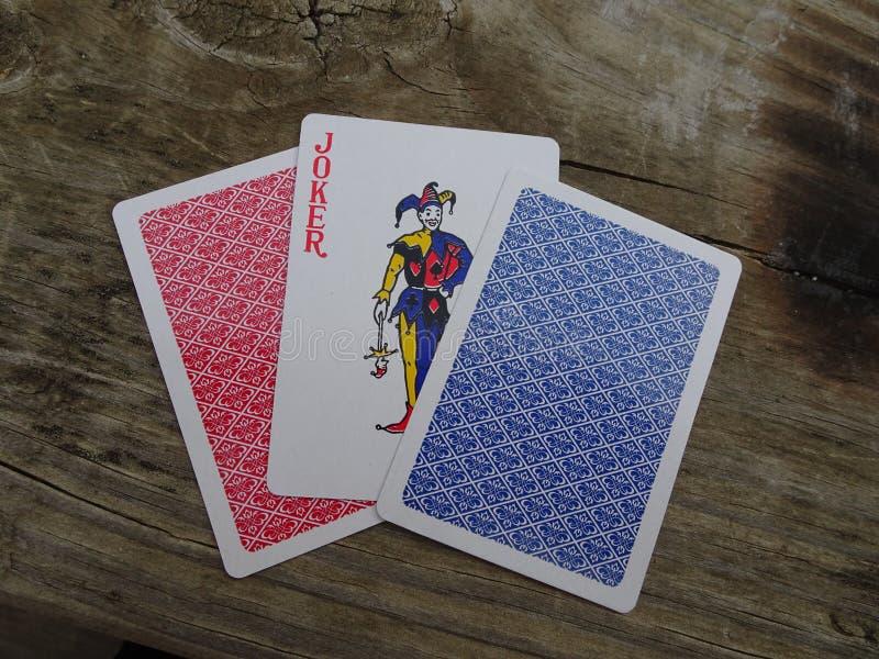 Joker tussen kaarten stock afbeeldingen