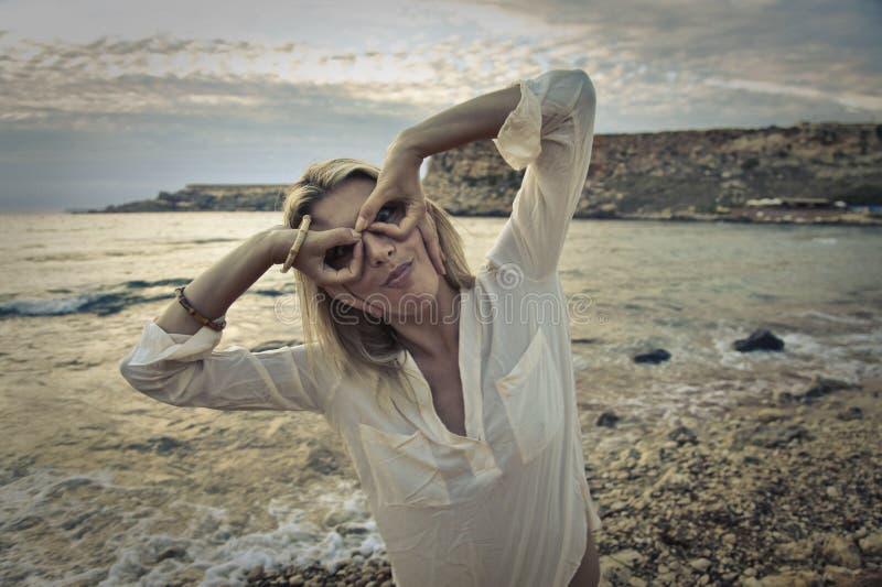 Jokes at the beach. Blonde woman making funny jokes at the beach stock photos