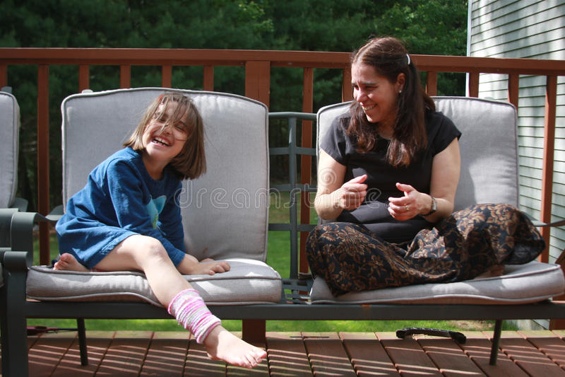 Jokes in Summer. An adorable little girl is laughing. Maybe she is kidding with her mom. They are sharing time together and enjoying a summer day royalty free stock photo