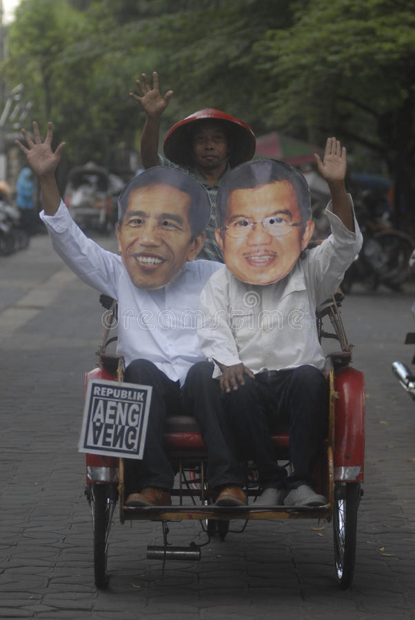 JOKOWI KALLA MASK. Political activist are wearing the mask of Indonesia's President Joko Widodo and his Vice President Jusuf Kalla to support their policy on the stock images