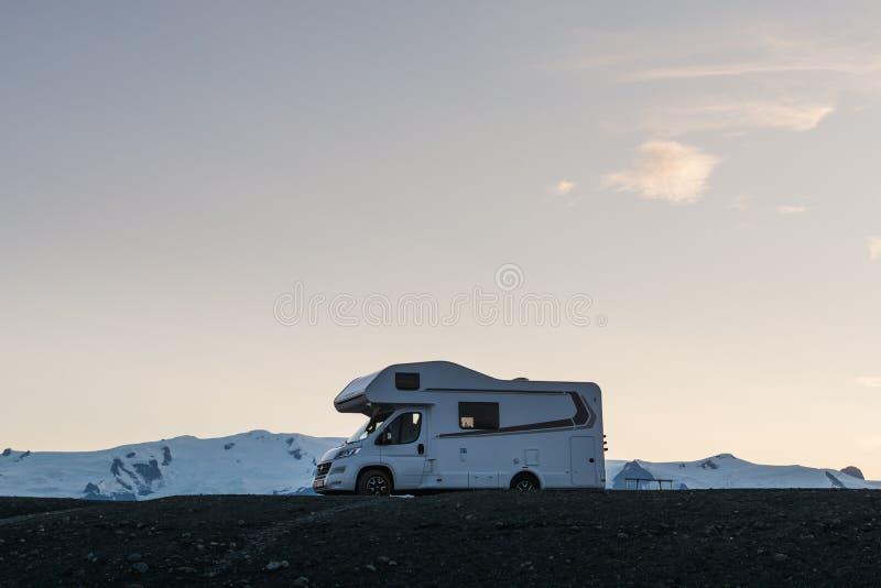 JOKULSARLON ISLAND - AUGUSTI 2018: Campervan parkerade på den svarta stranden på solnedgången med den korkade glaciären för snö i royaltyfri foto