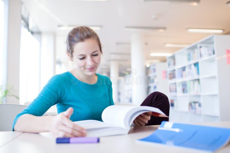 Joli étudiant universitaire féminin dans une bibliothèque images libres de droits