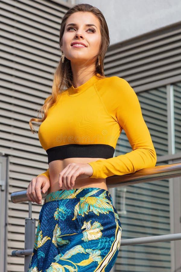 Joli attrayant et jeune femme posant sur la rue dans des vêtements colorés photos libres de droits
