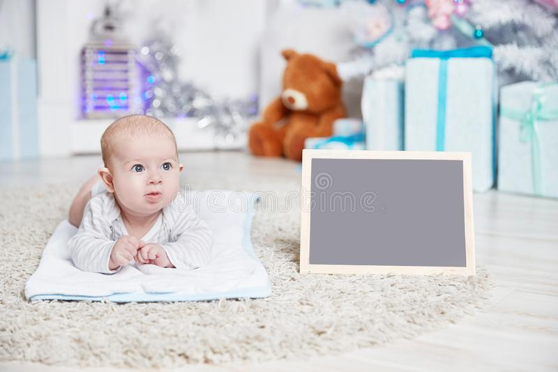 Joli bébé dans un salon confortable le réveillon de Noël photo libre de droits