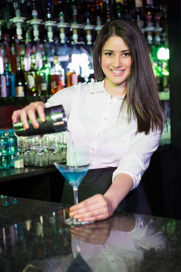 Joli barman versant une boisson bleue de martini dans le verre images stock