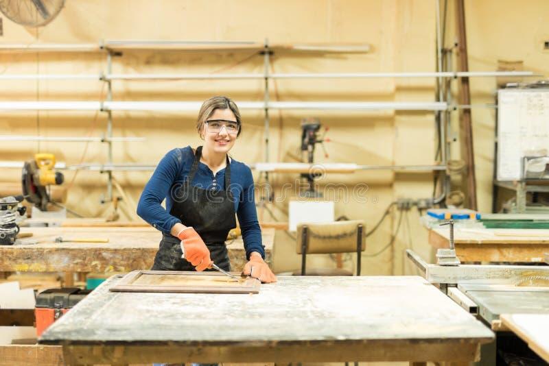 Joli charpentier employant une gouge en bois image stock