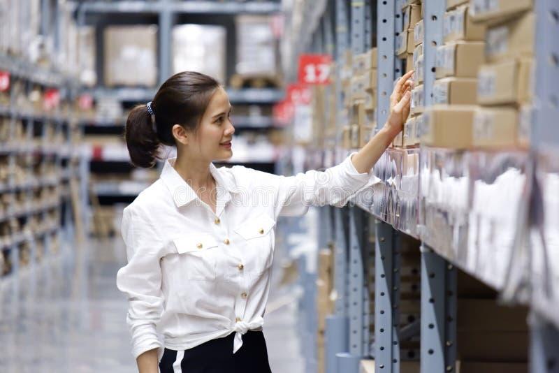 Joli client asiatique recherchant des produits dans l'entrep?t de magasin La fille employant son point de main au label pour v?ri images stock