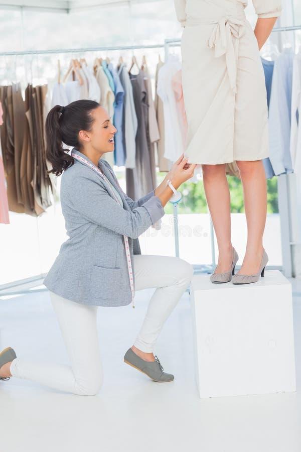 Joli couturier ajustant la robe sur un modèle photographie stock