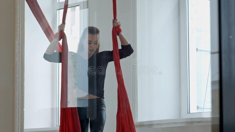 Joli danseur de poteau établissant dans la classe avec la soie aérienne image libre de droits