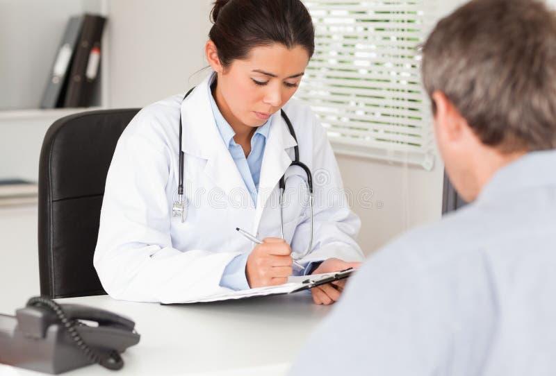 Joli docteur féminin consultant le patient photo stock