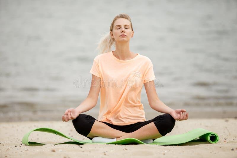 Joli emplacement de d?tente de jeune fille en position de lotus sur un tapis de yoga sur la plage sablonneuse un jour chaud image libre de droits
