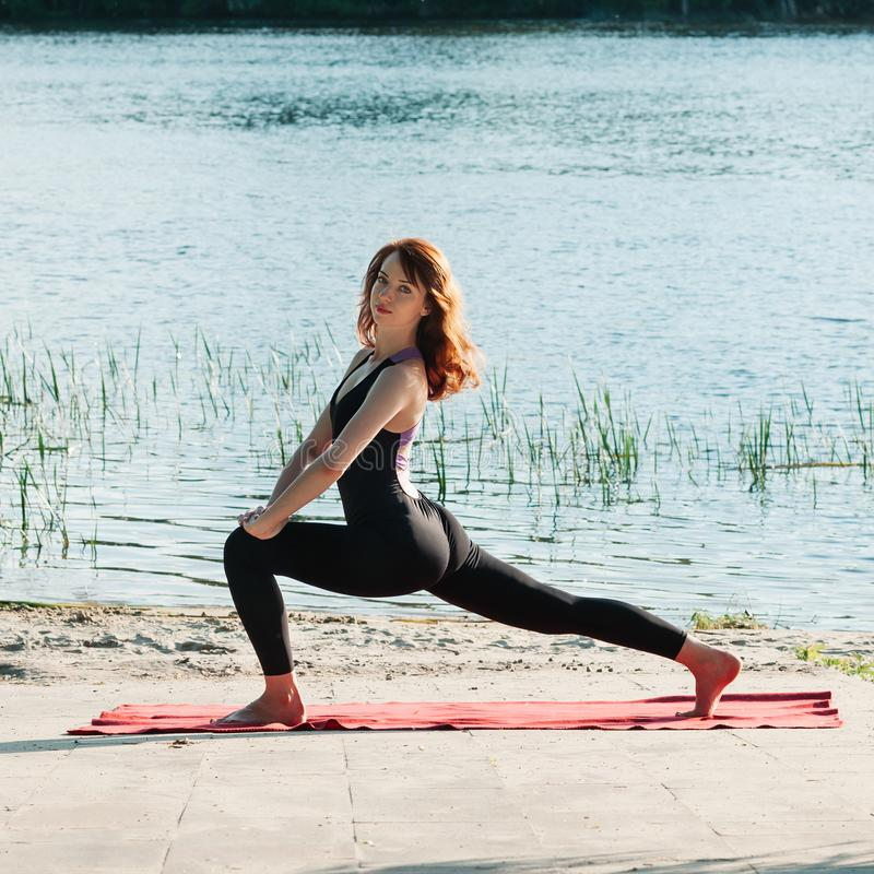 Joli exercice femelle convenable de yoga de pratique dehors image libre de droits