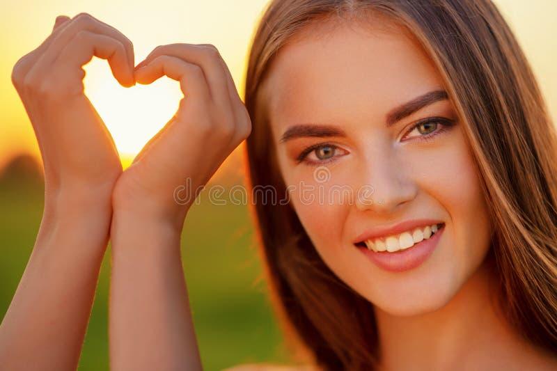 Joli faire des gestes joyeux de fille en forme de coeur au-dessus du backgrou de coucher du soleil photo libre de droits