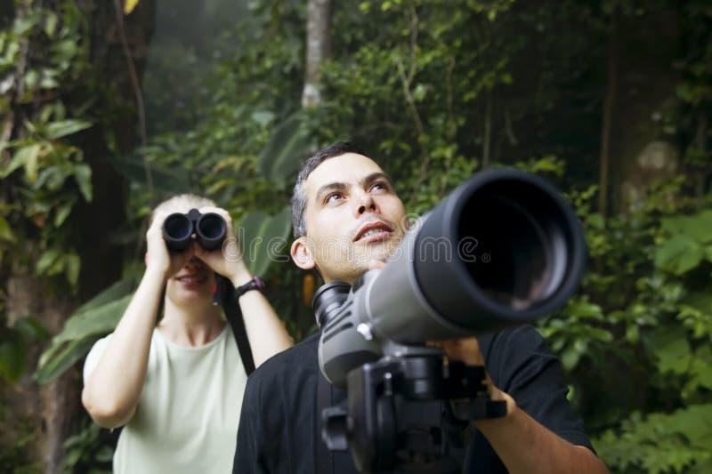 Joli femme avec les jumelles et l'homme avec Telescop images libres de droits