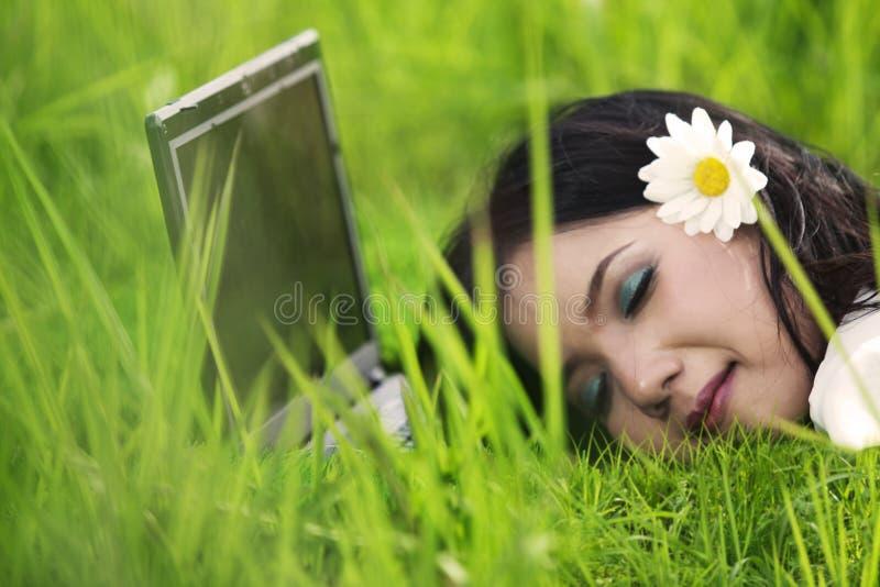 Joli femme dormant sur l'ordinateur portatif extérieur photo stock
