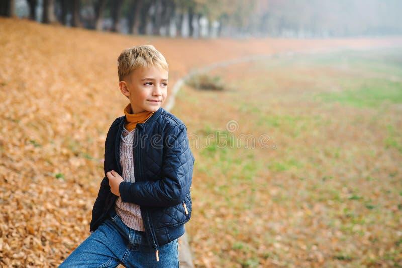 Joli garçon blond dans une promenade dans un parc d'automne Enfant élégant en plein air Un écolier vêtu de vêtements de mode posa photo stock