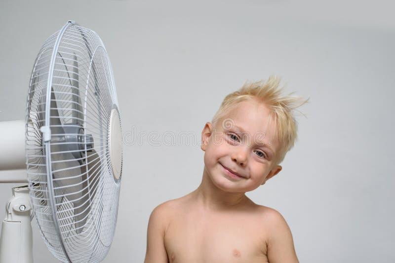Joli garçon blond de sourire avec les supports nus de torse près d'un ventilateur Concept d'?t? photo libre de droits