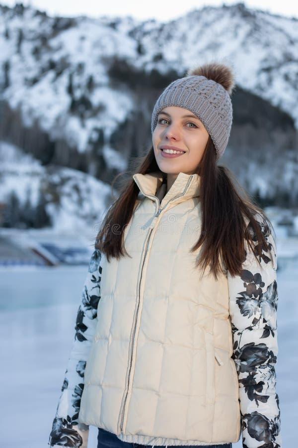 Joli hiver de patinage de glace de femme dehors, massage facial de sourire Montagnes à l'arrière-plan photographie stock