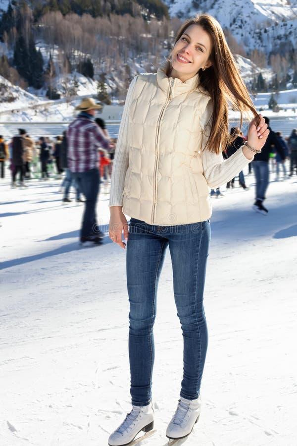 Joli hiver de patinage de glace de femme dehors, massage facial de sourire Montagnes à l'arrière-plan photos stock