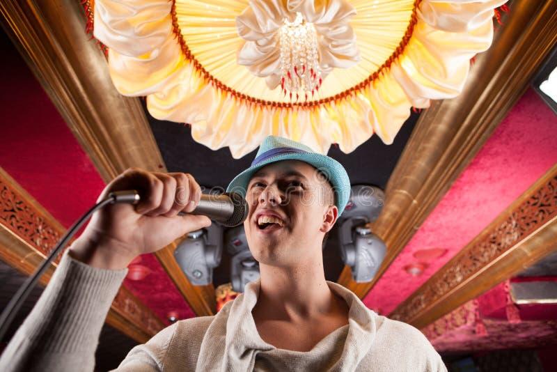Joli homme en gros plan chantant dans le microphone image libre de droits