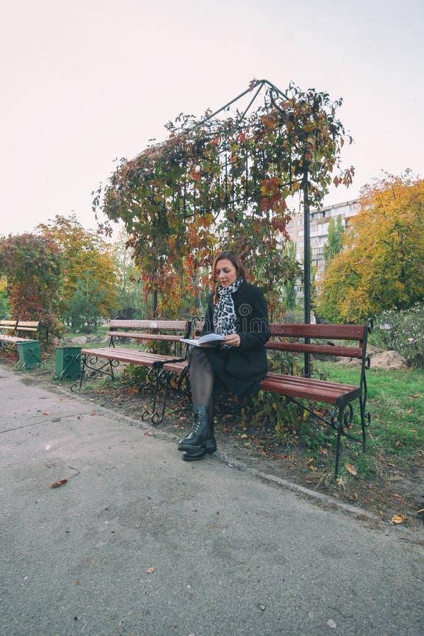 Joli jeune étudiant lisant un livre dehors sur le campus La fille lisant le livre sur le banc passe-temps, littérature photographie stock