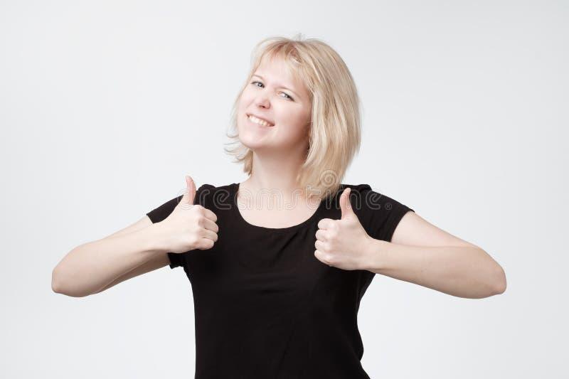 Joli jeune adolescent blond de sourire montrant des pouces  image stock