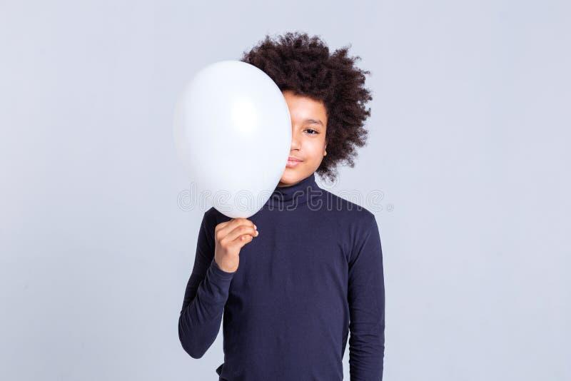 Joli jeune homme avec la moitié Afro de fermeture de coiffure de son visage avec le ballon photographie stock