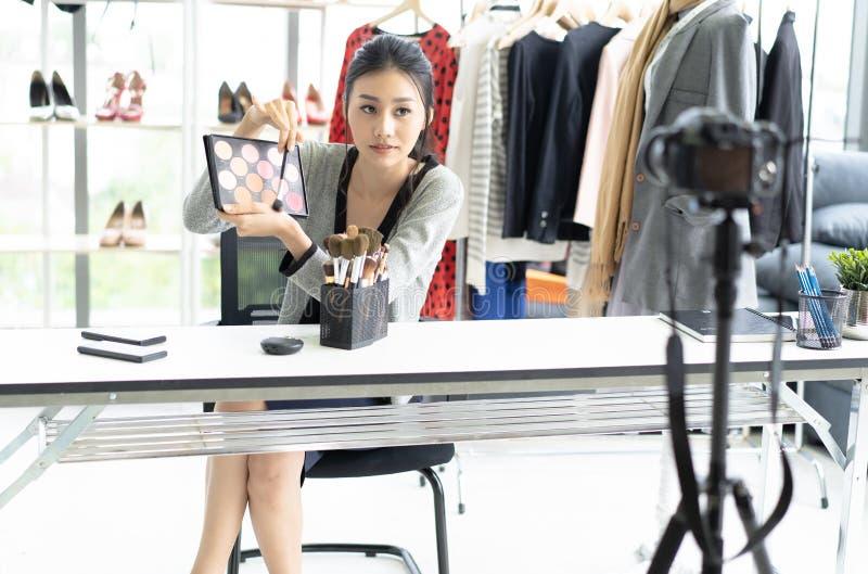 Joli jeune styliste asiatique de vlogger de femme tenir à disposition l'équipement cosmétique tout en enregistrant la vidéo et do image stock