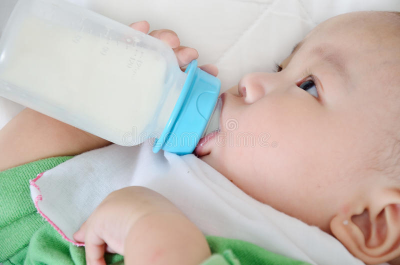 Joli lait boisson de bébé garçon de bouteille image libre de droits