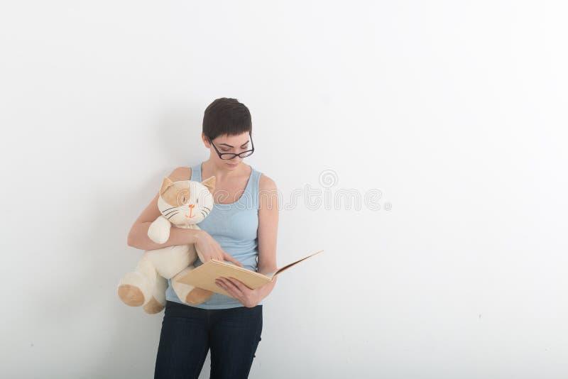 Joli livre de lecture de femme de brune avec son chat de jouet de peluche photographie stock libre de droits