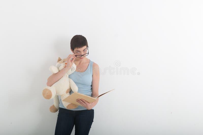 Joli livre de lecture de femme de brune avec son chat de jouet de peluche photos stock