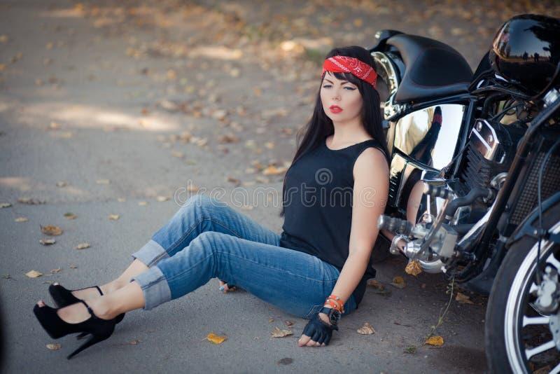 Joli motard de fille ou femme mignonne avec les jeans de port de cheveux élégants et longs se reposant sur le plancher à la moto image stock