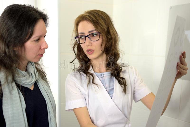 Joli opticien d'optom?triste d'ophtalmologue de jeune femme montrant des diagrammes d'essai d'acuit? visuelle et les expliquant a photographie stock