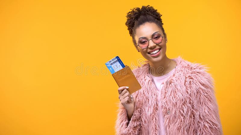 Joli passeport se tenant femelle avec des billets sur le fond lumineux, aventure photographie stock libre de droits